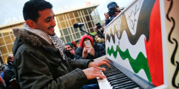 Syrian pianist Aeham Ahmad, winner of Beethoven Prize, plays during a rally outside the main railway...