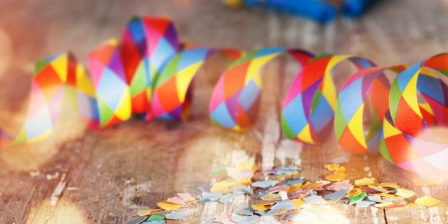 Colorful confetti and air streamer on rustic wooden table with