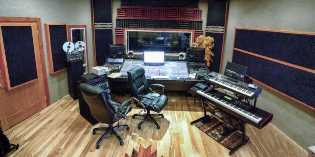 Wide angle shot of a modern high tech recording studio that includes various methods of recording, digital...