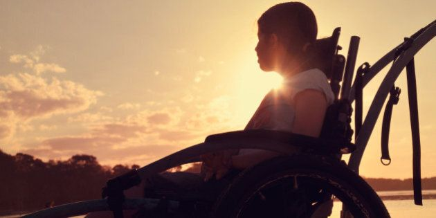 Teenage girl with cerebral palsy sits in a wheel chair watching the sunset by a