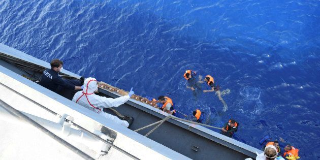 Migrants from a capsized boat are rescued during a rescue operation by Italian navy