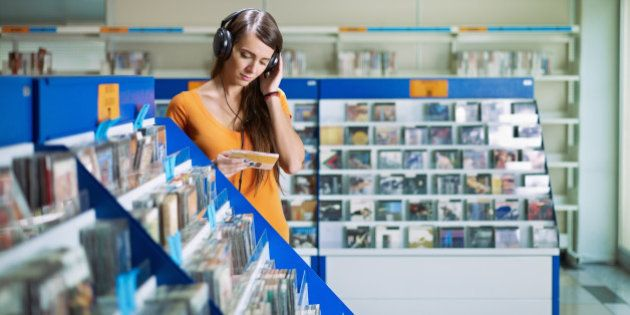 caucasian woman with headphones, choosing cd in music shop. Horizontal shape, front view, waist up, copy
