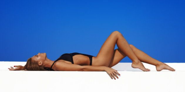 Sexy fashion model in swimwwear with skined body against blue sky on