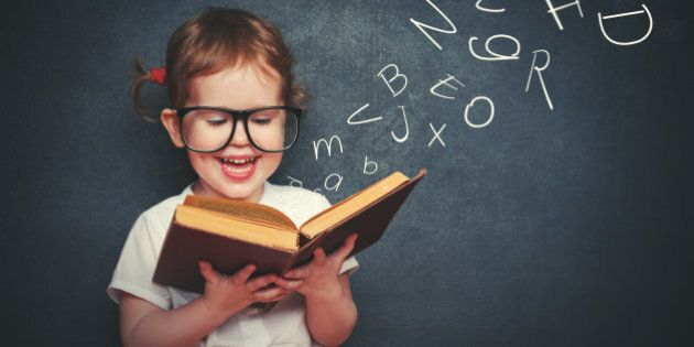 cute little girl with glasses reading a book with departing letters about
