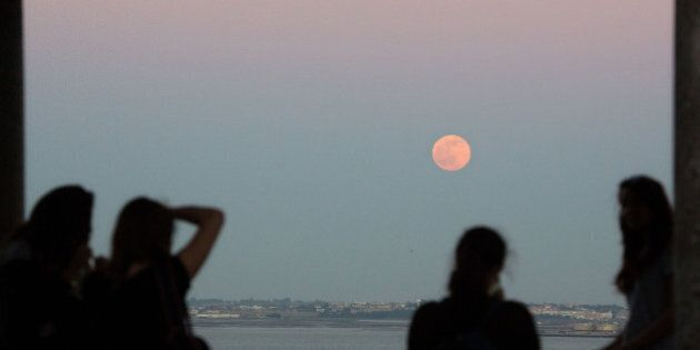 A group of girls watches a full Strawberry Moon, or Rose Moon, rise above the Tagus river in Lisbon Tuesday,...