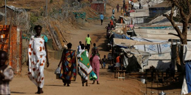 Internally displaced people walk on a road close to the outer perimeter of a United Nations Mission in...