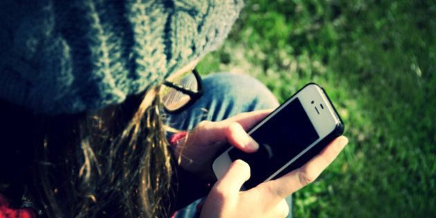 A teenager holding and using a mobile