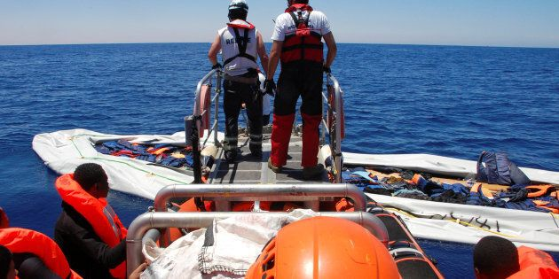 Nick Romaniuk (L) and Max Avis of the NGO SOS Mediterranee take a last look at a rubber boat that they...