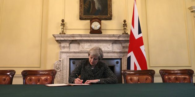 British Prime Minister Theresa May in the cabinet, sitting below a painting of Britain's first Prime...