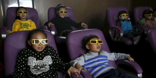 Children watch a 3D war movie at a community theatre in Hefei, Anhui province, March 29, 2015. Picture...