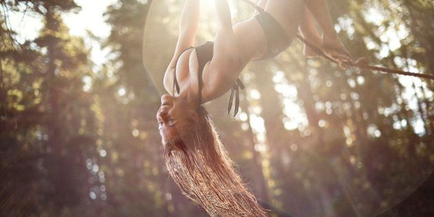 Young girl hanging upside down from a rope with the sun flaring behind