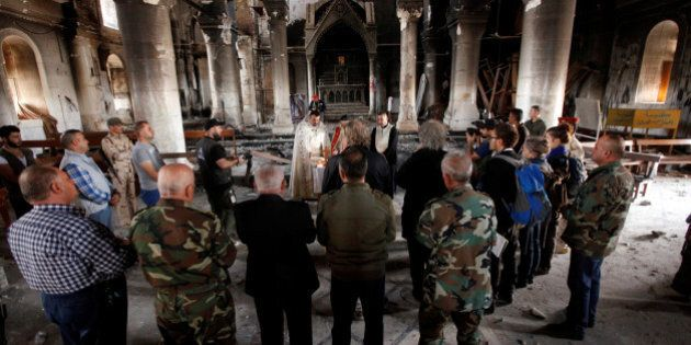 Iraqi priests hold the first mass at the Grand Immaculate Church since it was recaptured from Islamic...