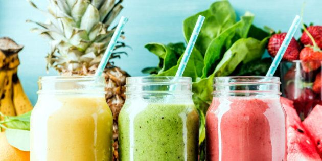 Freshly blended fruit smoothies of various colors and tastes in glass jars. Yellow, red, green. Turquoise...
