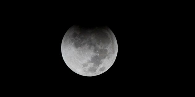 Earth's shadow begins to obscure the view of a so-called Supermoon during a total lunar eclipse over...