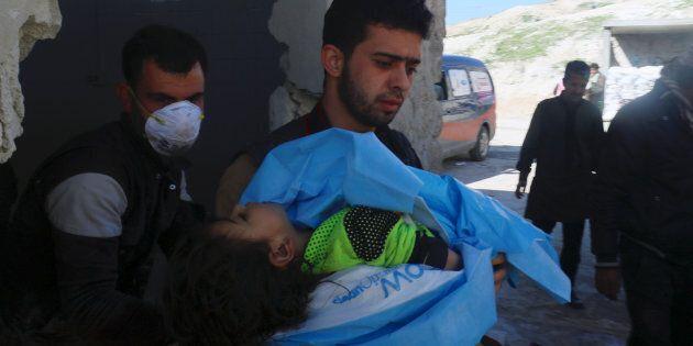 I soccorritori portano via il corpo di un bambino morto a Khan Sheikhoun, in