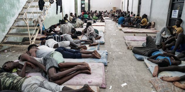 TOPSHOT - Illegal immigrants are seen at a detention centre in Zawiyah, 45 kilometres west of the Libyan...