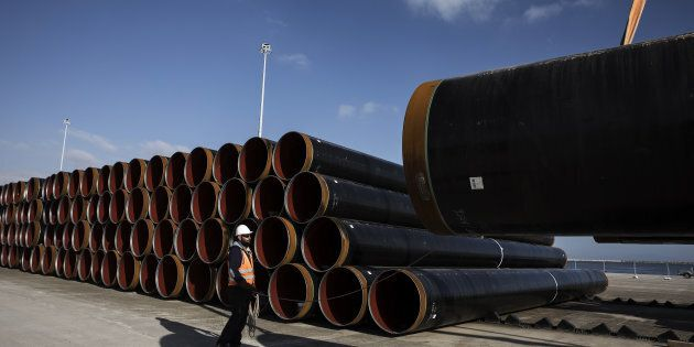 A worker holds a rope as he guides the loading of a pipe section for the Trans Adriatic gas pipeline...
