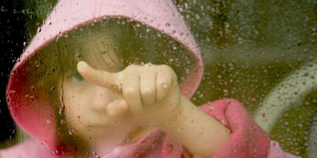 Girl looking through a foggy wet