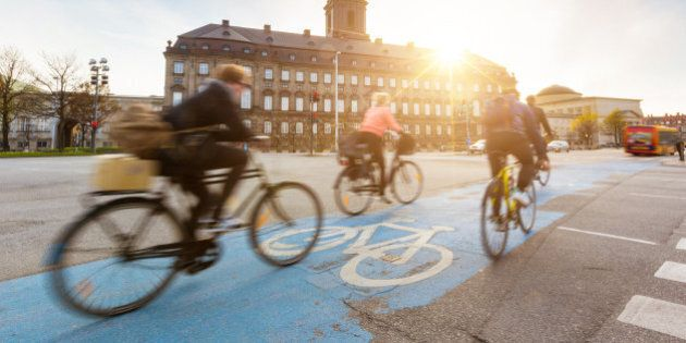 Blurred people going by bike in Copenhagen, with Christiansborg palace on background. Many persons prefer...