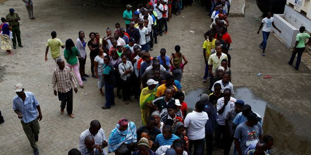 People queue to cast their votes at a polling station during the presidential election in Mombasa, Kenya...