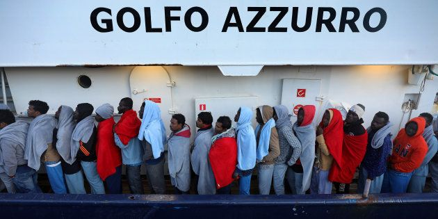 Migrants line up as they wait to be processed by Italian authorities aboard the former fishing trawler...