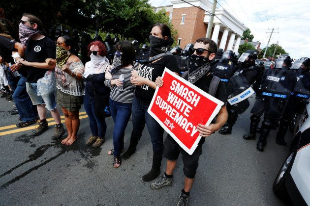 Counter-protesters lock arms in the middle of a street as police try to disperse them, after members...
