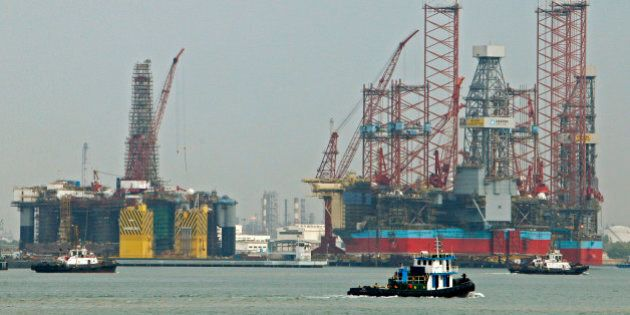 Tugboats pass jack-up rigs at a Keppel FELS shipyard in Singapore January 21, 2014. Singapore's Keppel...