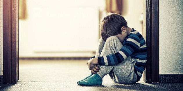 Depressed sad child sitting on the floor, in the door. The little boy is hiding his head between