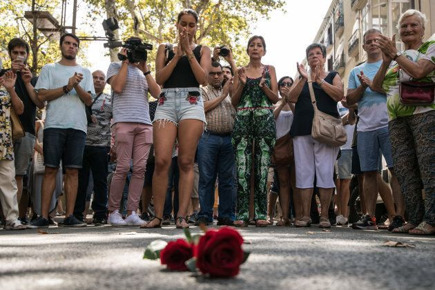 BARCELONA, SPAIN - AUGUST 18: People gather around roses laid on the ground on Las Ramblas after a one...