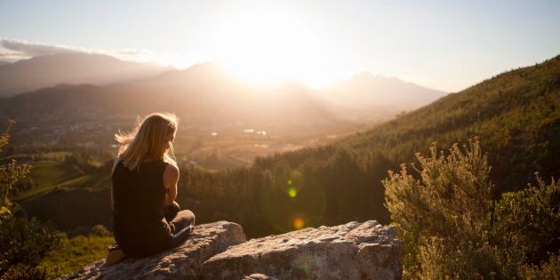 Woman sitting on mountain and looking at