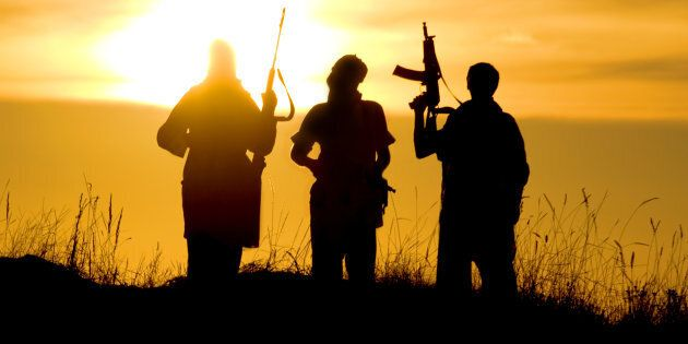 Silhouettes of several soldiers with rifles against a