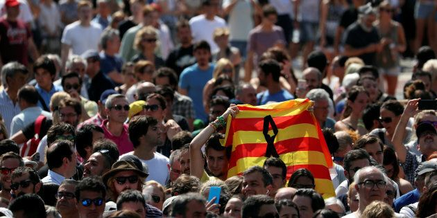 A man holds a Catalan flag as people gather to osberve a minute of silence at Placa de Catalunya, a day...