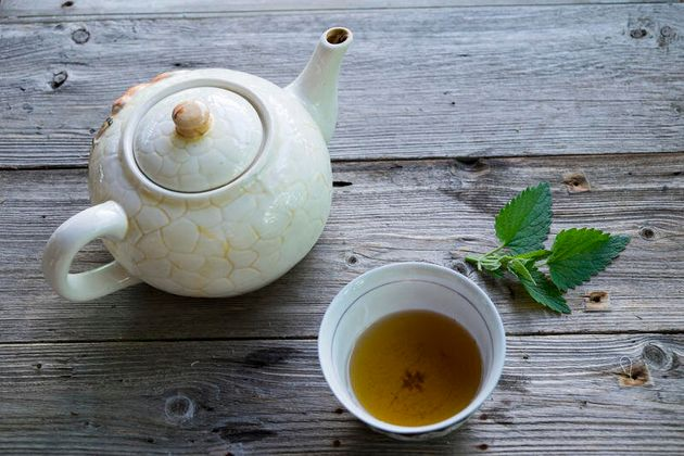 Cup of green tea with mint leaf and teapot Cup of green tea with mint leaf and