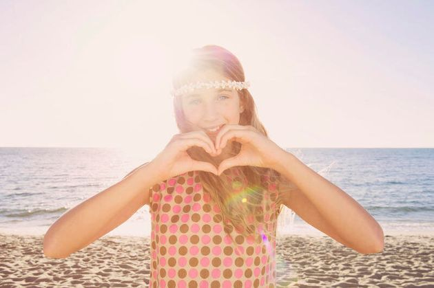 Caucasian girl making heart shape with hands on beach Caucasian girl making heart shape with hands on