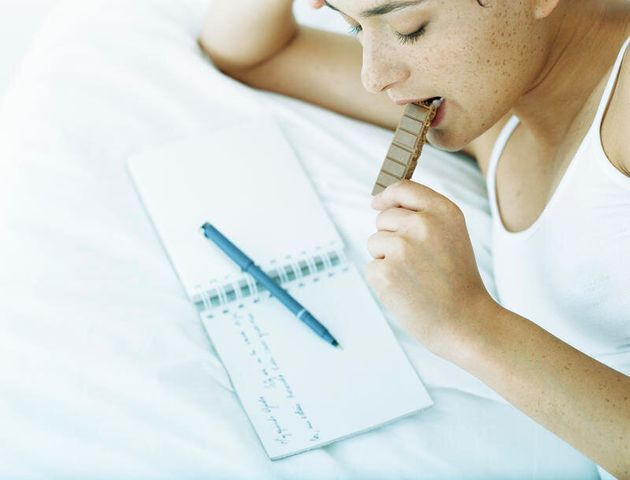 Woman lying on side on bed eating chocolate and looking down at notebook with pen lying across it Woman...