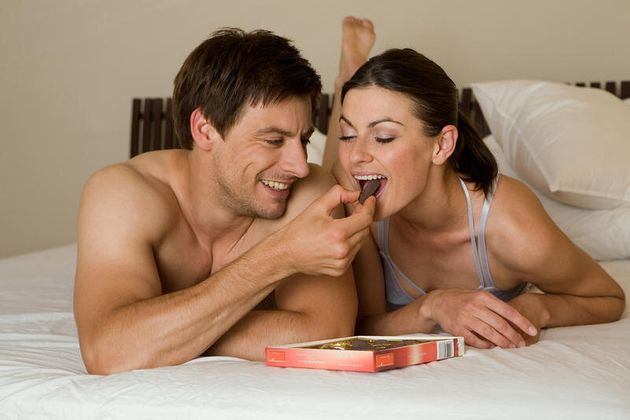 Couple eating sweets in bed. Couple eating sweets in