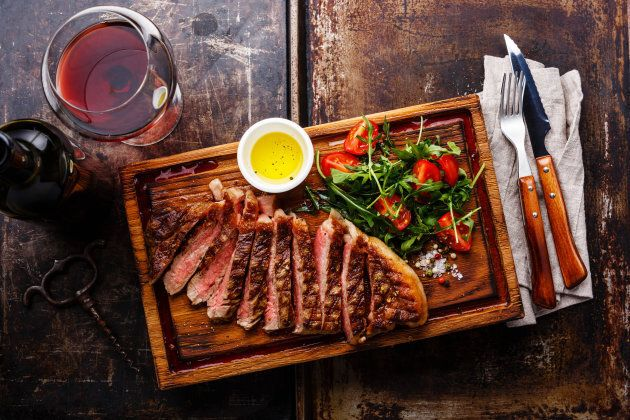Sliced grilled beef barbecue Striploin steak and salad with tomatoes and arugula on cutting board and...