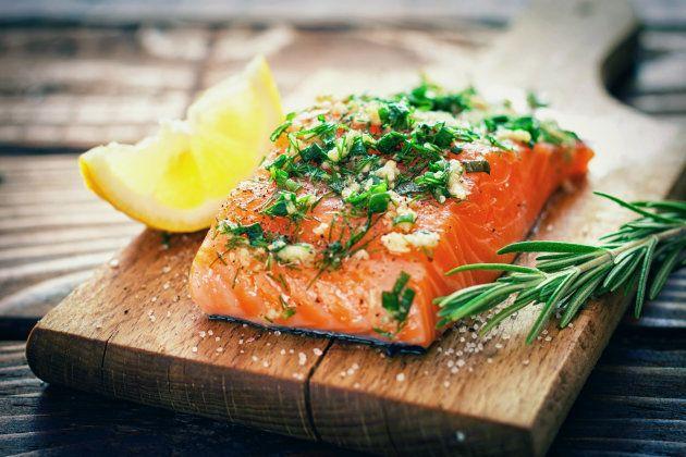 Raw salmon on a cutting board with fresh