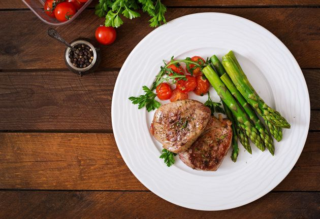 Barbecue grilled beef steak meat with asparagus and tomatoes. Top