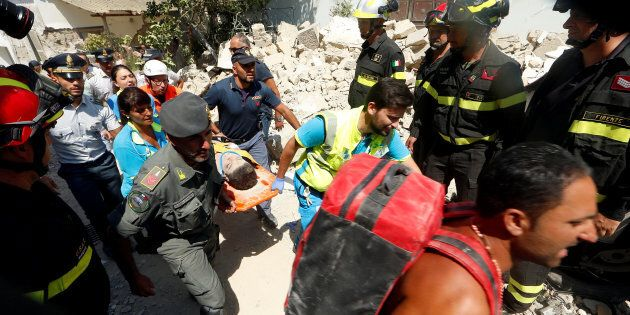 Rescue workers carry a child after an earthquake hits the island of Ischia, in Naples, Italy August 22,...