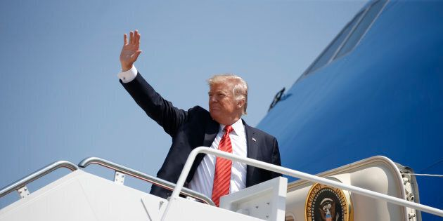 U.S. President Donald Trump waves while boarding Air Force One before departing for Arizona from Joint...