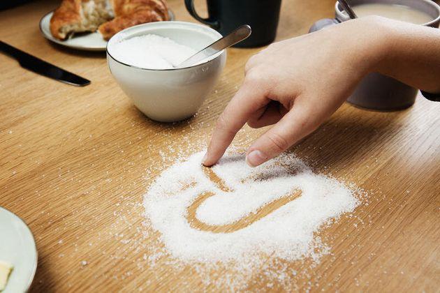 Girl drawing hart in sugar on table Girl drawing hart in sugar on