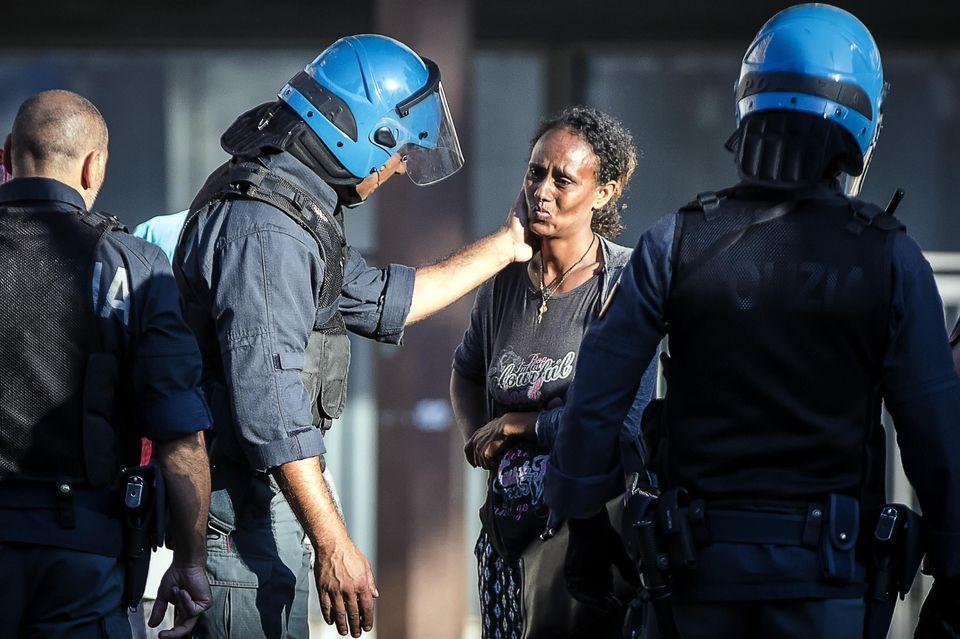 Il poliziotto fa una carezza alla migrante: questa foto restituisce un po' di luce alla vergogna di