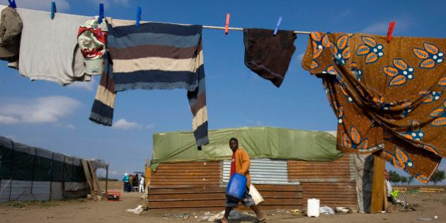 An African immigrant walks past a shack in a makeshift camp in the countryside near the village of Rignano...