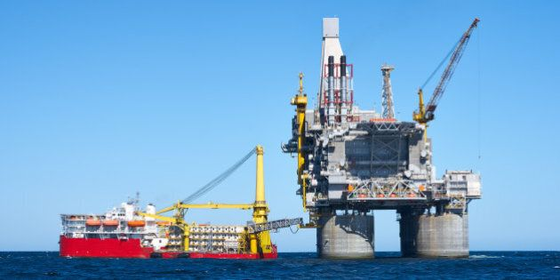Oil rig and support vessel on offshore area. Blue sky, sea.