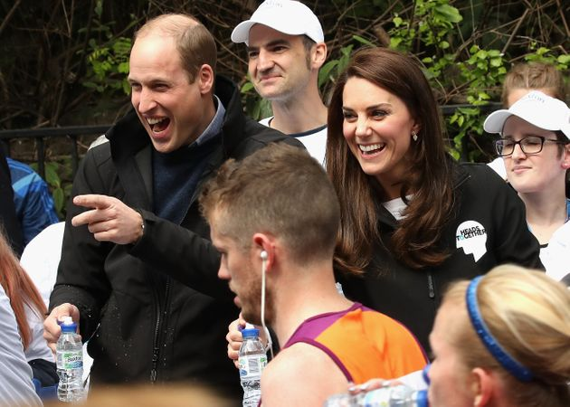 Britain's Prince William, Duke of Cambridge is sprayed with water by a runner as Britain's Catherine,...