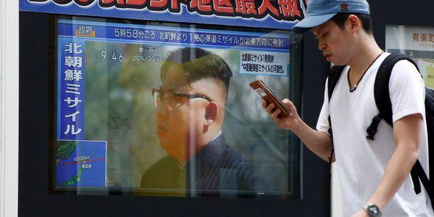 A man walks past a TV set showing North Korea's leader Kim Jong-Un in a news report about North Korea's...