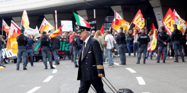 An Alitalia crew member walks past Alitalia employees who take part in a strike at Fiumicino international...