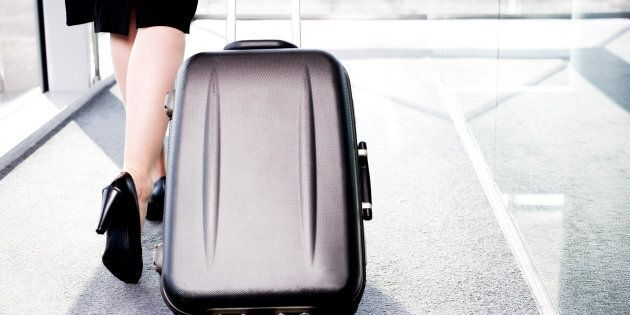 Businesswoman traveling, pulling suitcase along inside station or