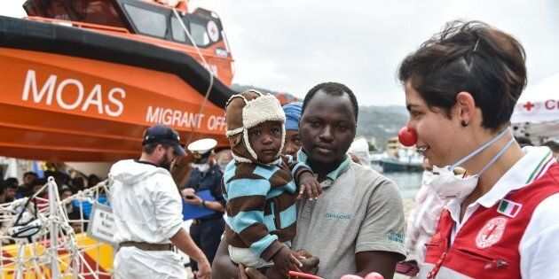 A volunteer of the Italian Red Cross welcomes a man and his baby as they disembark from a rescue ship...
